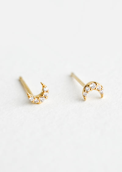 A pair of very tiny gold stud earrings in the shape of crescent moons, covered in clear crystals.