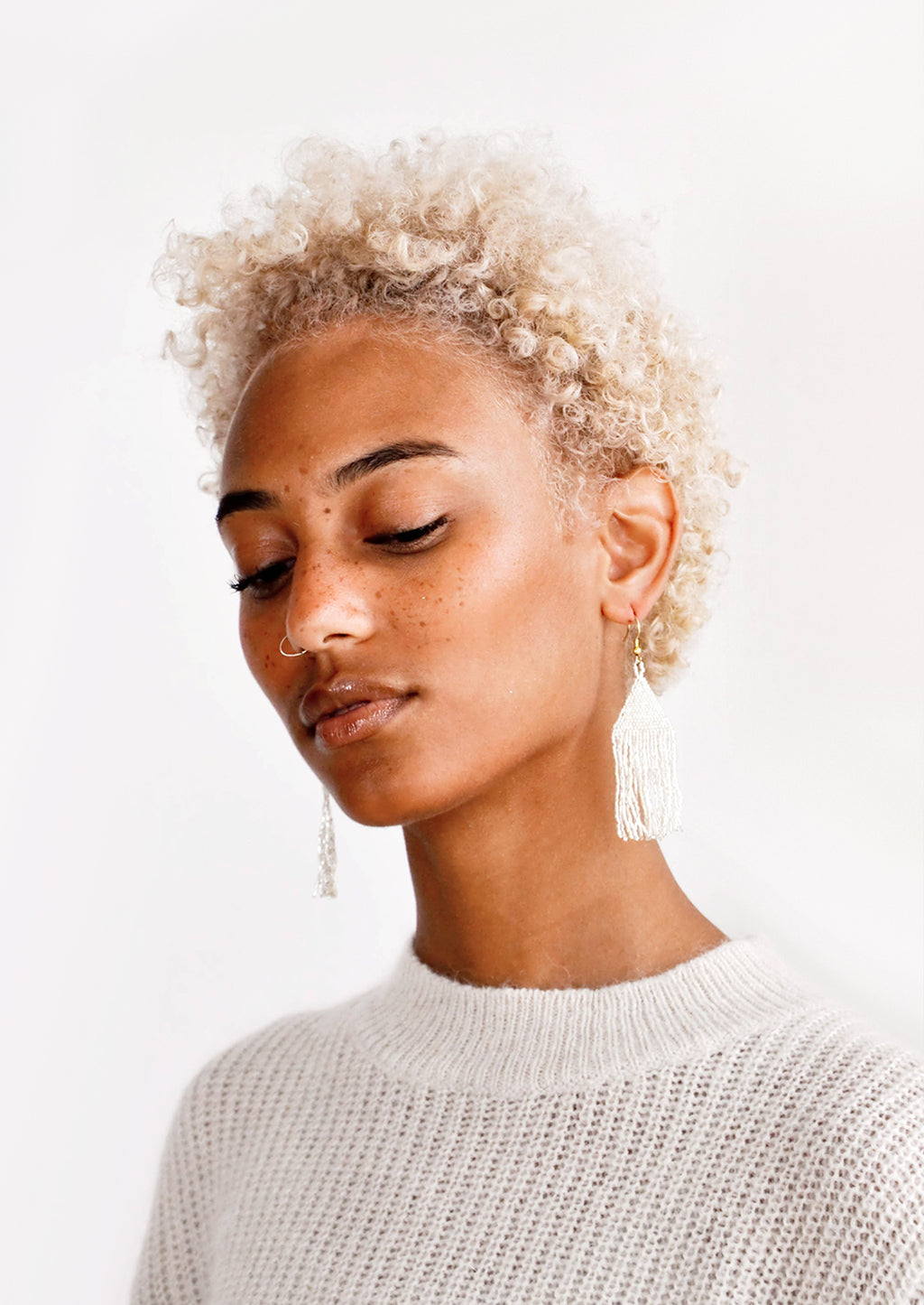 4: Model wears silver fringe beaded earrings and sweater.