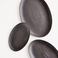 1: Oval-shaped, black ceramic trays with radiating lines pattern in a mix of incremental sizes