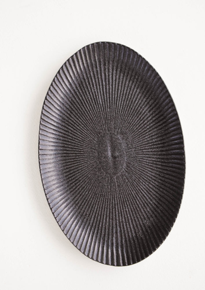 3: Oval-shaped, black ceramic tray with radiating lines pattern