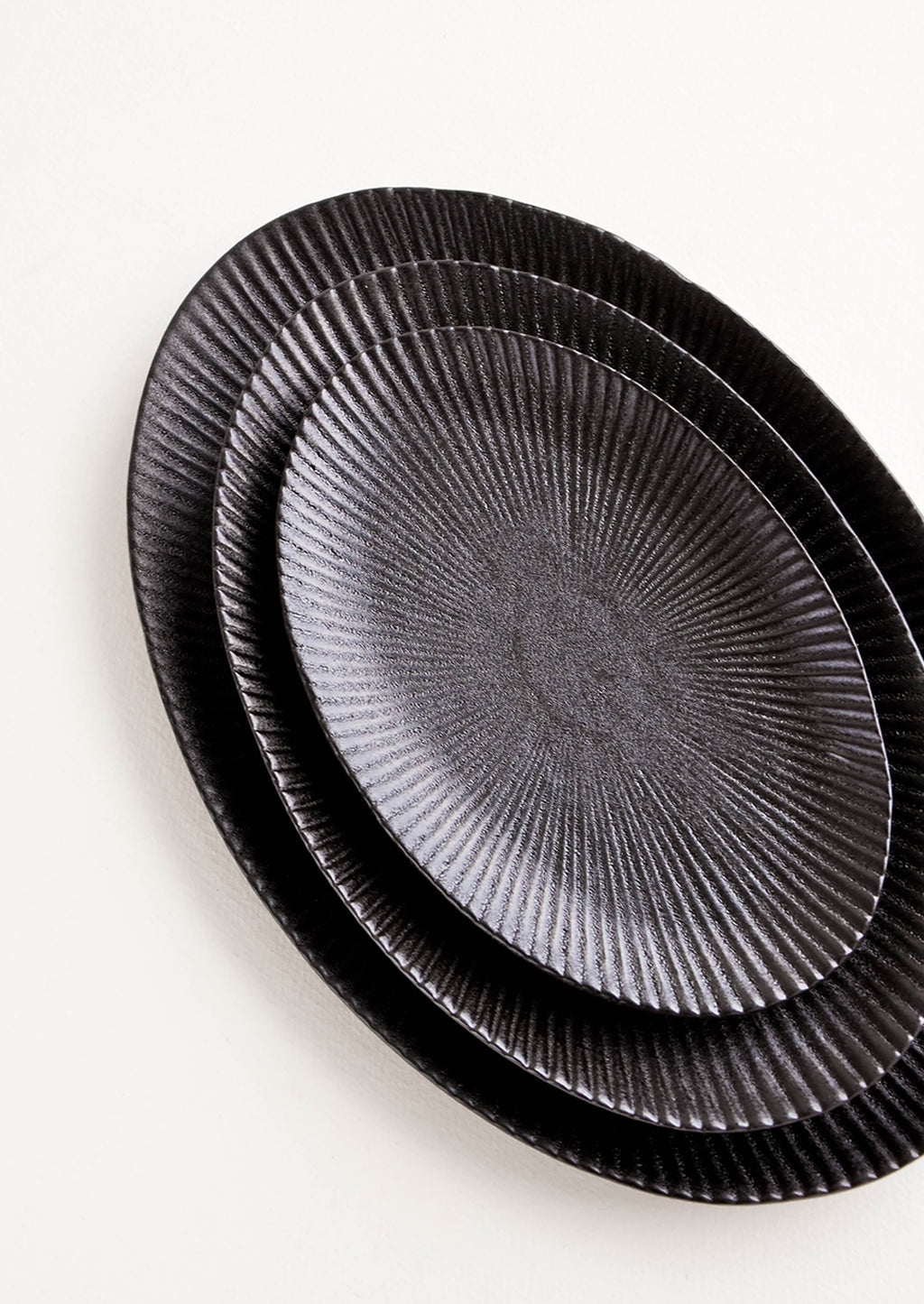 2: Oval-shaped, black ceramic trays with radiating lines pattern stacked in incremental sizes