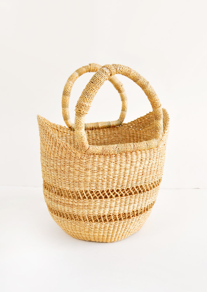 1: Petite decorative basket woven from natural grass, with two handles at top. Features an airy, open weave stripe detail.