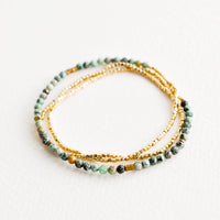 African Turquoise: A single strand bracelet of gold and multi-colored turquoise beads wrapped upon itself in three layers.