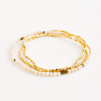 White Fossil: A single strand bracelet of gold and ivory beads wrapped upon itself in three layers.
