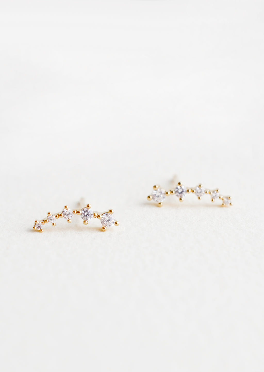 1: Stud earrings with clear crystals in incremental sizes, designed to climb up the ear
