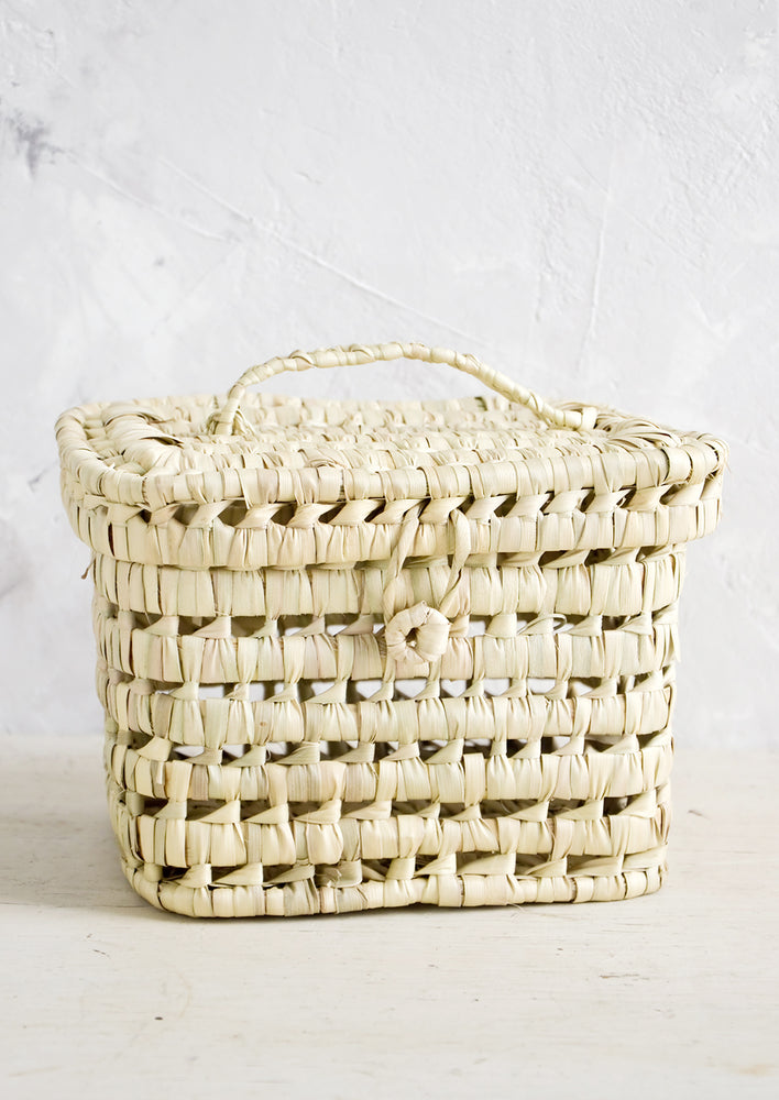 3: A square-shaped, lidded basket made from woven natural palm leaf.