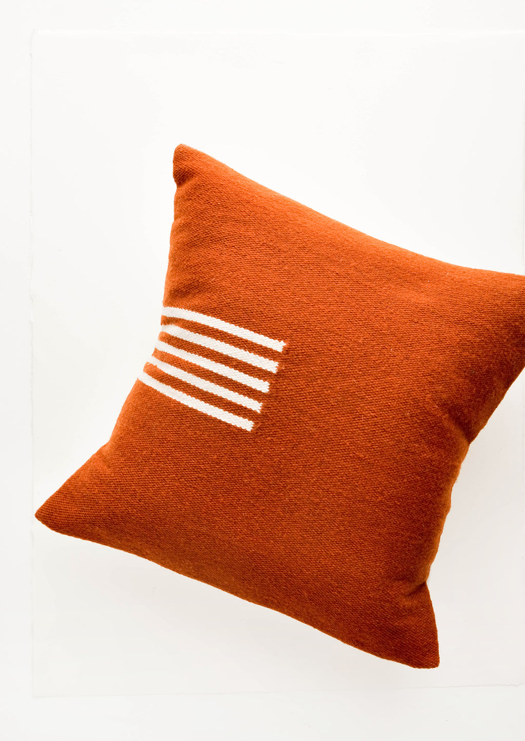 Terracotta / Natural: Terracotta colored, square wool throw pillow with contrasting small stripe detail at side.