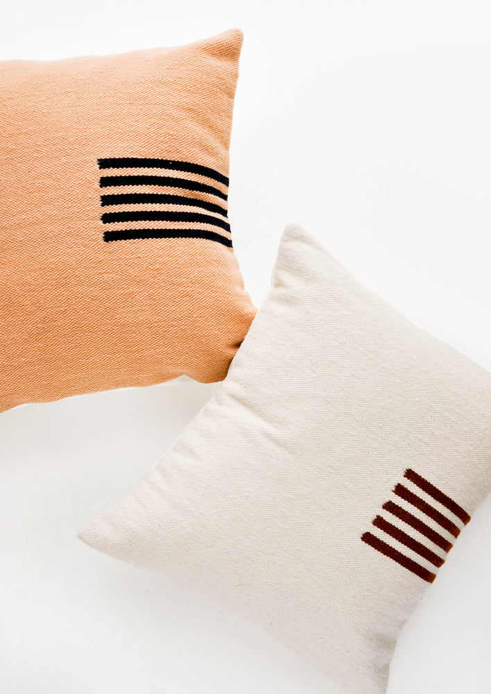 1: Square wool throw pillows with contrasting small stripe detail at side.