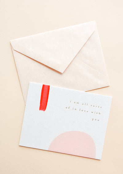 "A pale tan envelope and white greeting card with a rectangle of red paint, a semicircle of pink paint, and gold foil text reading ""I'm all sorts of in love with you."""