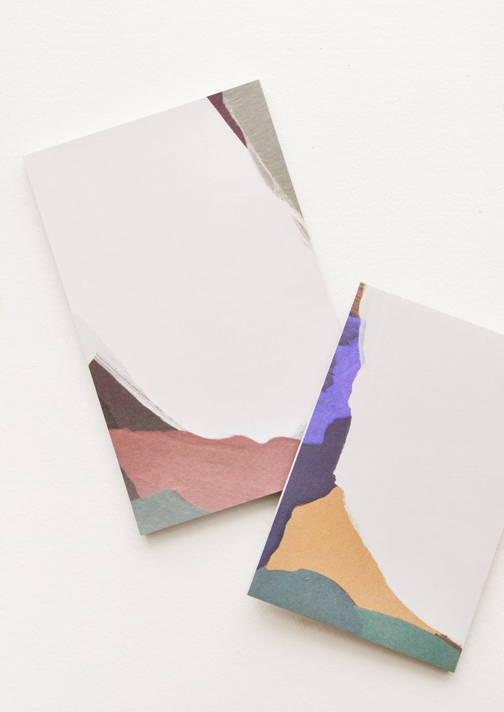 4: Two notepads, decorated with colorful abstract shapes.