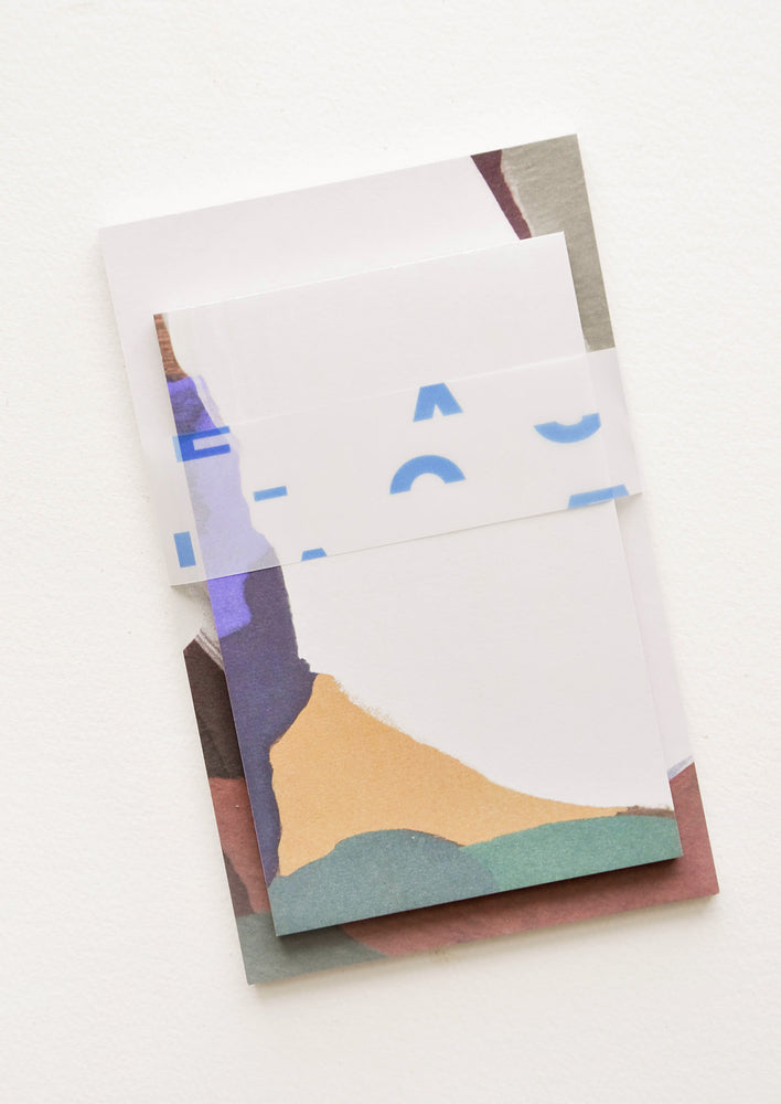 Fjord Multi: Two stacked notepads wrapped with cellophane, decorated with colorful abstract shapes.
