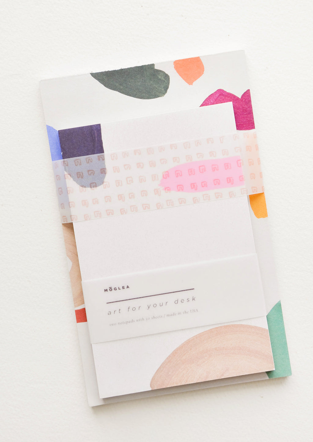 Brights Multi: Two stacked notepads wrapped with cellophane, decorated with colorful abstract shapes.