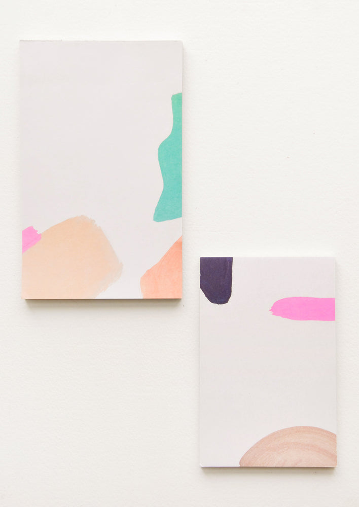 3: Two notepads, decorated with colorful abstract shapes.