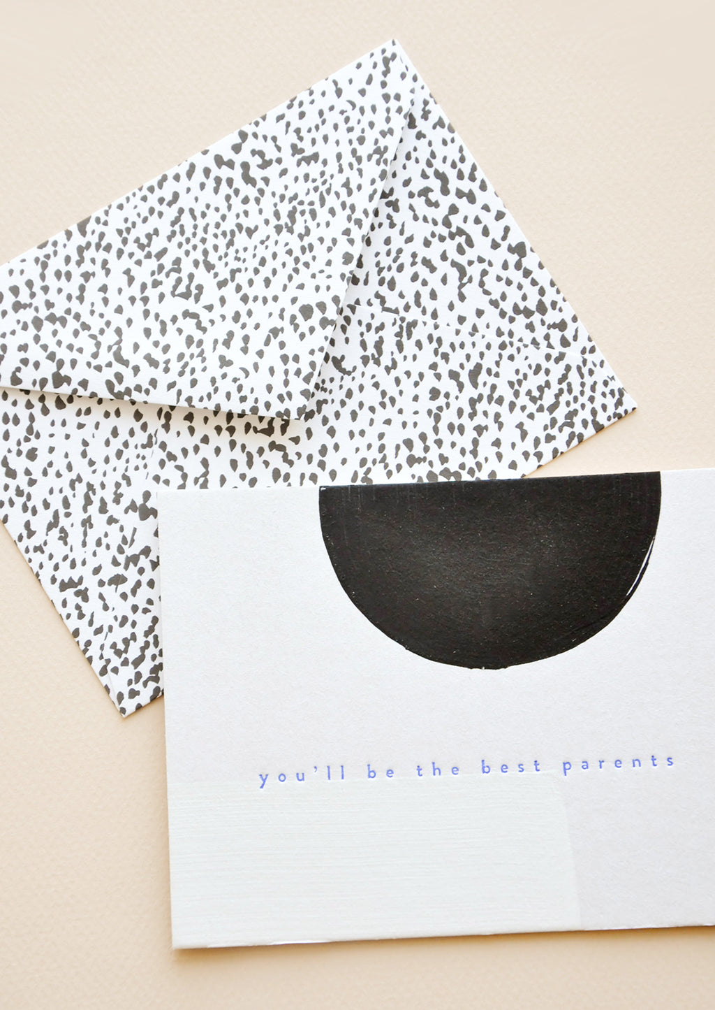 "2: A black and white dotted envelope and white greeting card with a black semicircle and the text ""you'll be the best parents"" in blue."