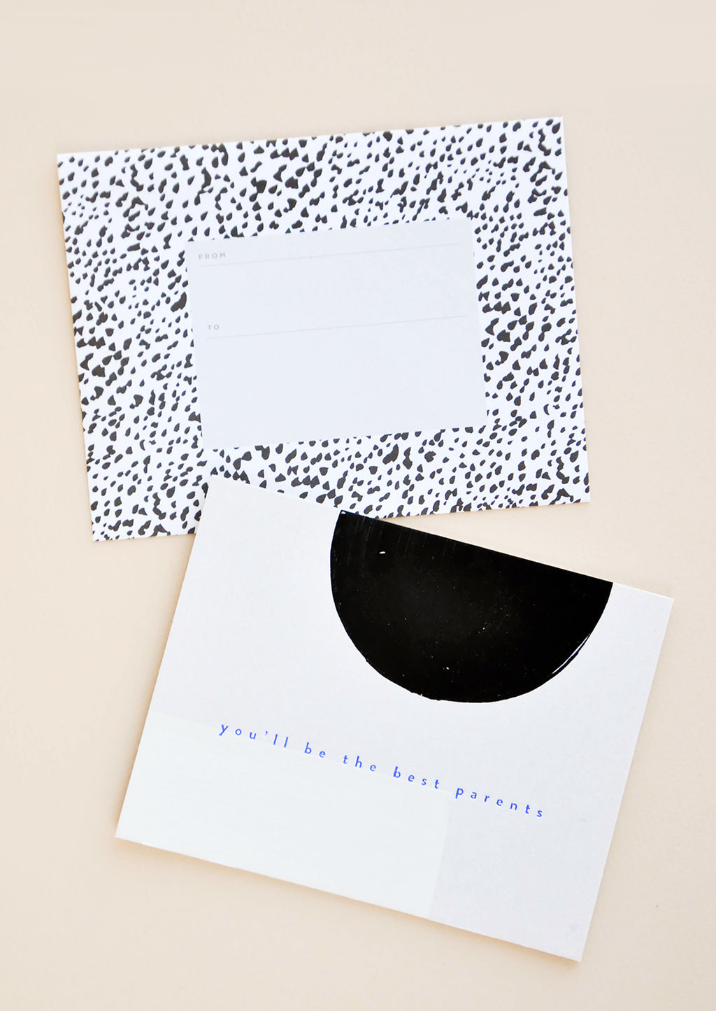 "1: A black and white dotted envelope and white greeting card with a black semicircle and the text ""you'll be the best parents"" in blue."