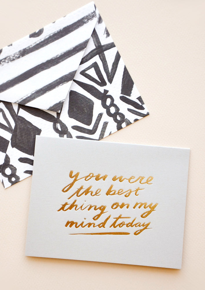 "1: Grey greeting card with ""You were the best thing on my mind today"" in gold foil. Shown with black and white patterned envelope."