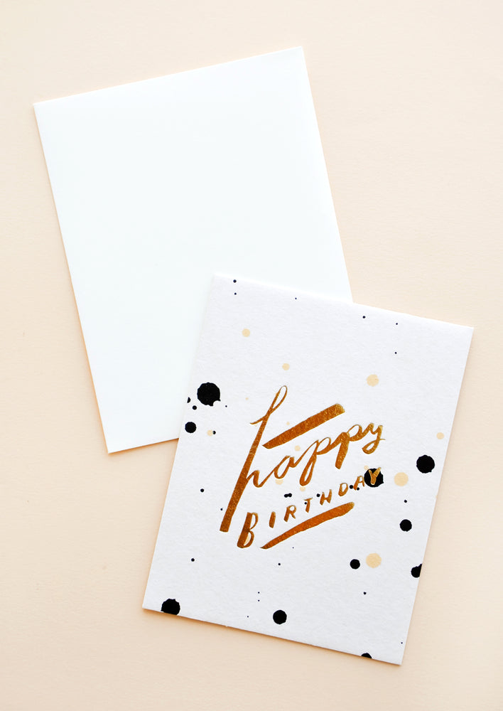 "1: A white envelope and white greeting card with black and gold paint splatter and the words ""happy birthday"" in gold foil."