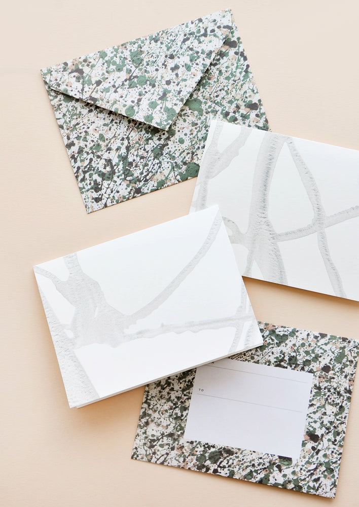 1: Two envelopes patterned with green and gray paint splatter alongside two white greeting cards with thin strokes of gray paint.