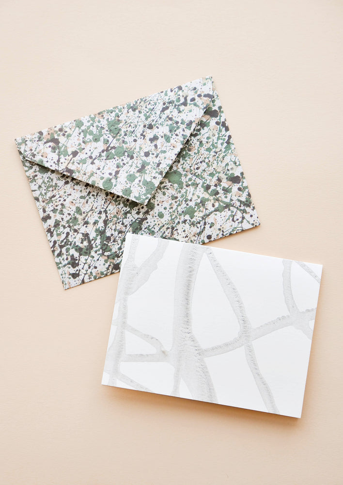 2: An envelope patterned with green and gray paint splatter and a white greeting cards with thin strokes of gray paint.