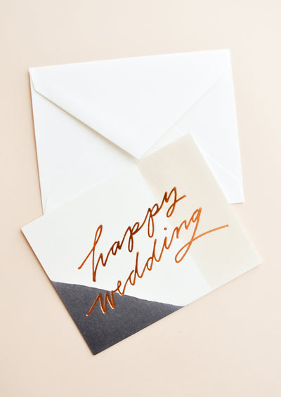 "Notecard with tricolor decoration and the words ""happy wedding"" in metallic script, with white envelope."