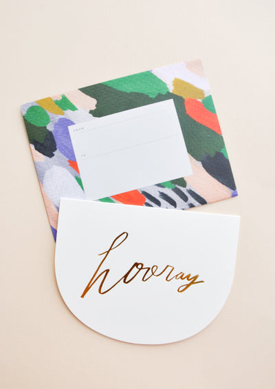 "A colorful patterned rectangular envelope with an accompanying greeting card in a white semicircle with gold foil script reading ""hooray."""