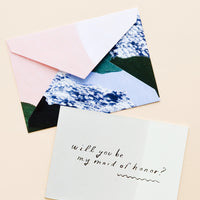 "Maid of Honor: Greeting card dipped in grey watercolor with silver text ""Will you be my maid of honor?"", paired with abstract printed envelope"