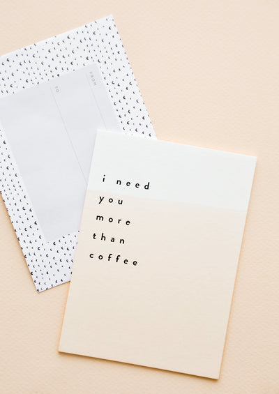 "Notecard with pale watercolor peach wash and the text ""I Need You More Than Coffee"" and dotted envelope."