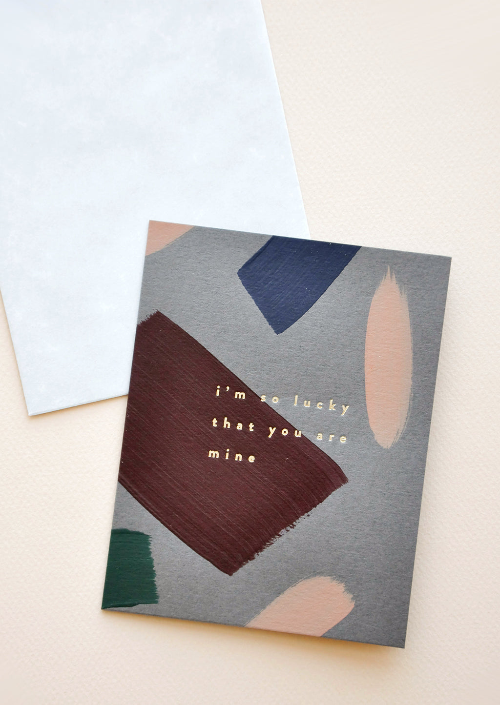 "1: A dark gray greeting card with maroon, pink, green, and navy patches of paint and the phrase ""so lucky that you are mine"" in gold foil."
