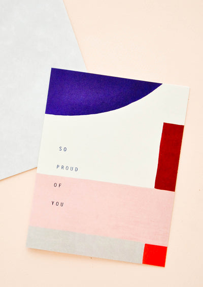 "Notecard with cobalt blue and pink/red geometric composition, and text ""So Proud Of You"""