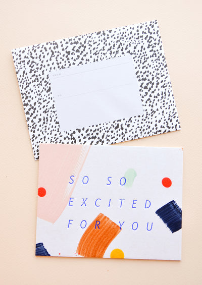 "Notecard with colorful abstract shapes and the text ""So So Excited For You"", with spotted black and white envelope"