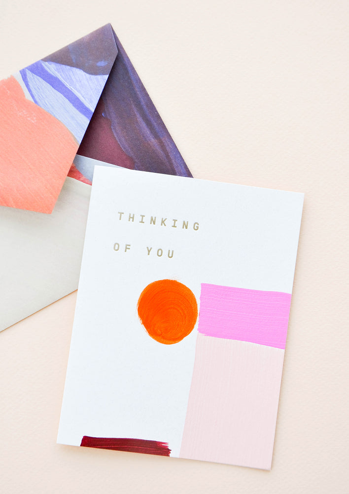 "2: Painted shapes in shades of pink on white greeting card with words ""Thinking Of You"" in gold foil. Shown with envelope painted with abstract lines."