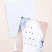 "1: A greeting card with paint strokes in white, pale rust, and navy with the lowercase words ""you are my home"" in copper foil."