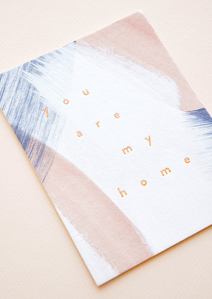 "2: A greeting card with paint strokes in white, pale rust, and navy with the lowercase words ""you are my home"" in copper foil."