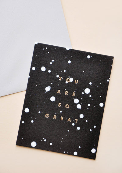 "Black greeting card speckled with white paint splatters and the words ""you are so great"" in gold foil."