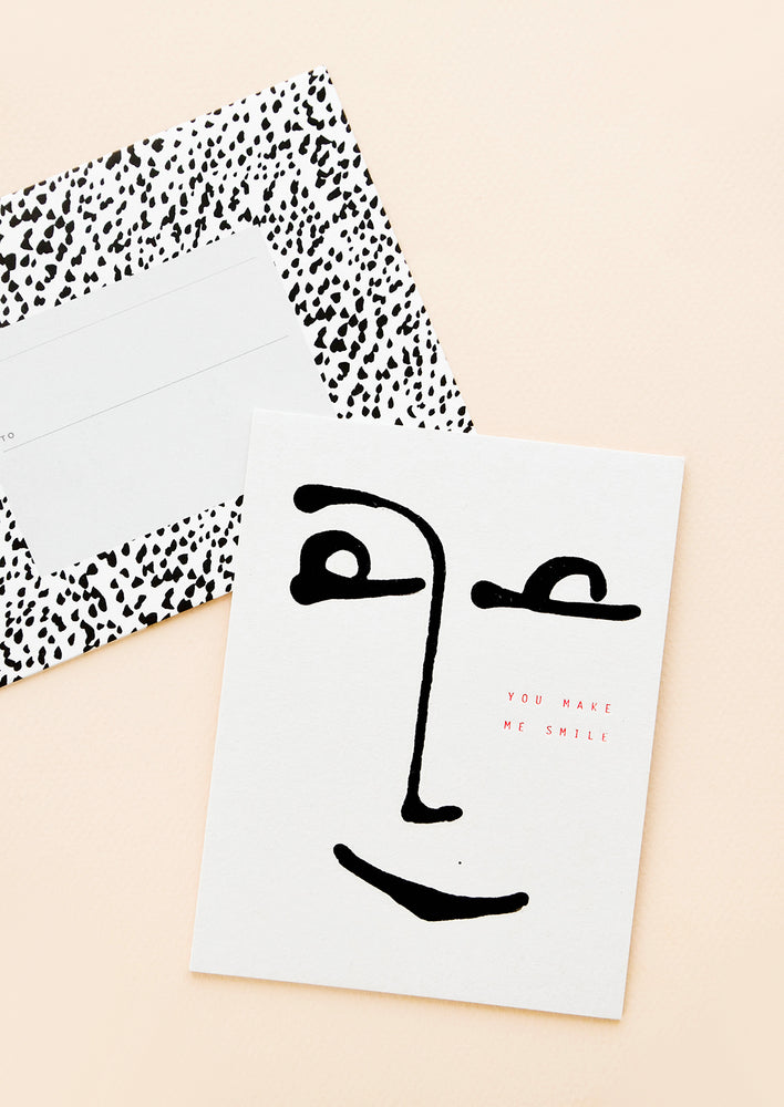 1: A black and white polka dot envelope and a white greeting card with a minimalist image of a smiling face.
