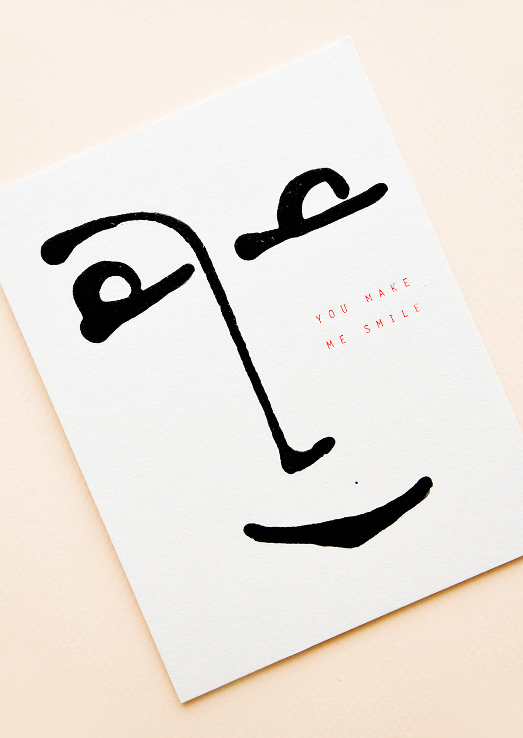 "2: White minimalist greeting card with a simple black drawing of a smiling face and the words ""you make me smile"" in gold foil."