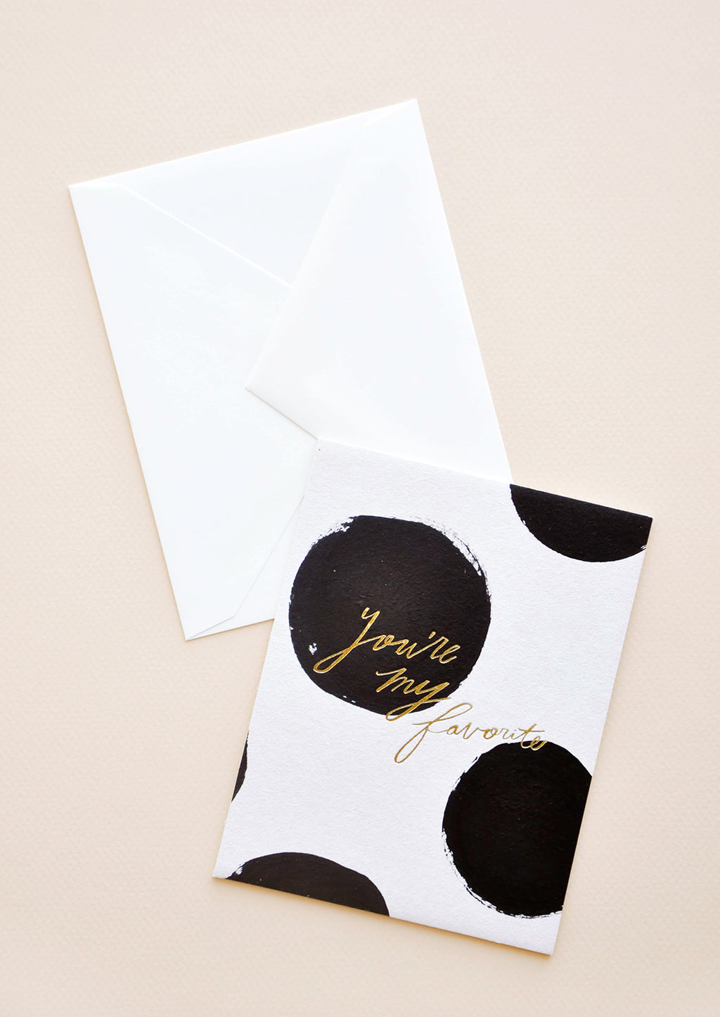 "1: Notecard with large black dots on white background and the text ""You're my favorite"" in gold, with white envelope."