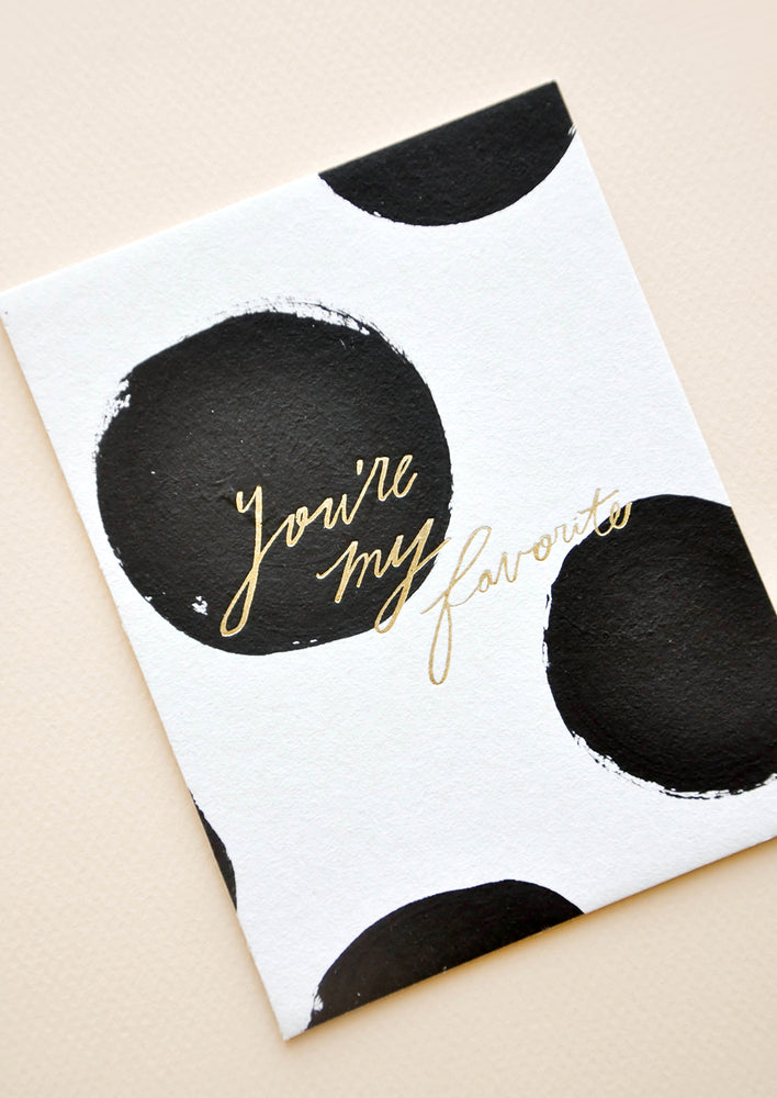 "2: Notecard with large black dots on white background and the text ""You're my favorite"" in gold."