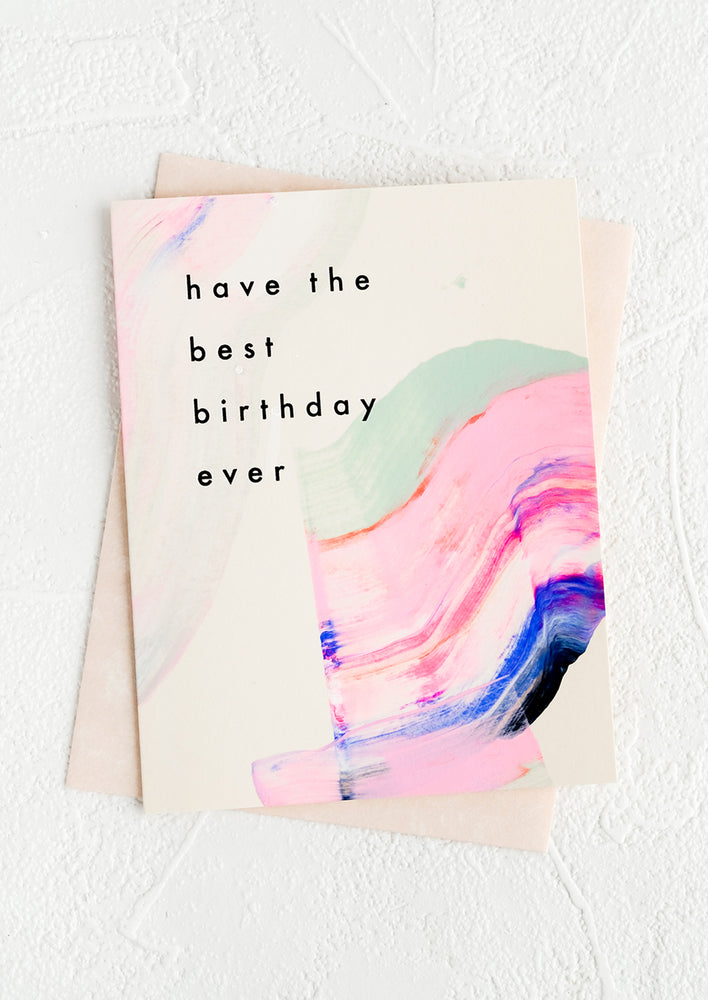 "1: A greeting card with hand-painted streak of paint and black lettering reading ""Have the best birthday ever"""