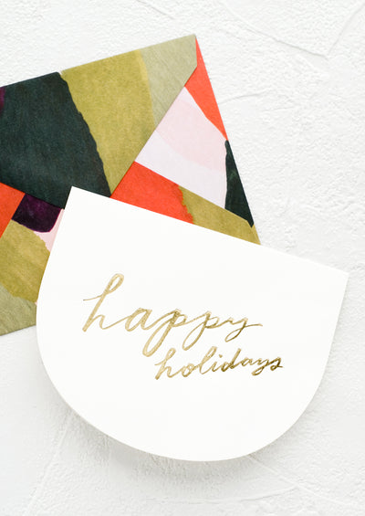"Greeting card in curved shape with gold script reading ""Happy holidays"", paired with green and red abstract envelope."