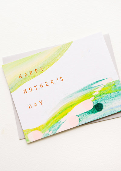 "Greeting card with hand-painted streaks of color and copper text reading ""Happy Mother's Day"""