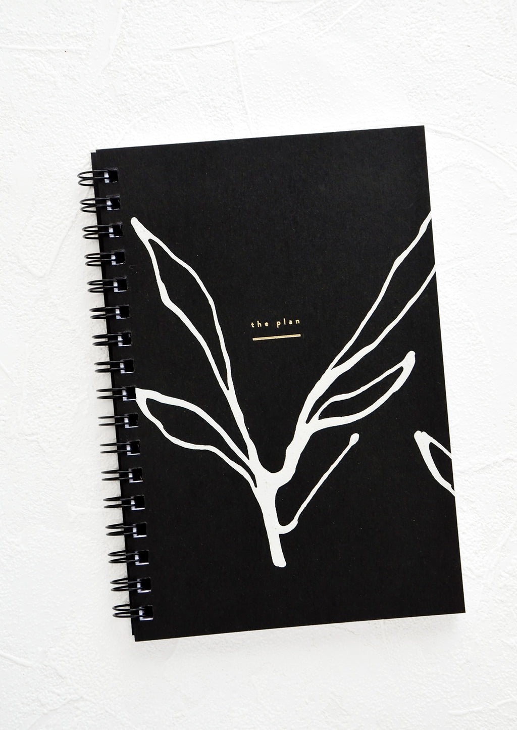 Seaweed Stroke: Spiral bound planner with black cover and hand-painted, abstract seaweed outline in white