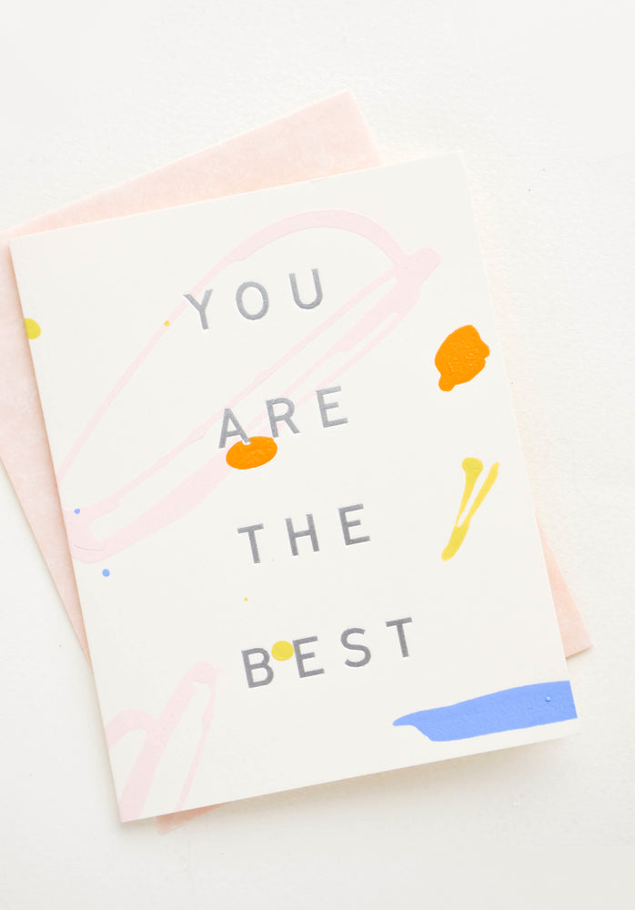"1: Greeting card with colored paint strokes and drips, silver lettering reads ""You Are The Best"""