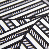2: A close up of textured layers of paper in black and white creating a geometric pattern.