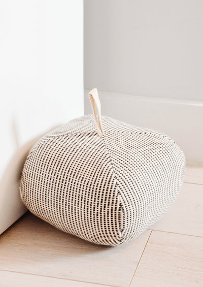 Cube-shaped upholstered doorstop, crafted in black and white dash print fabric with cotton loop at top.