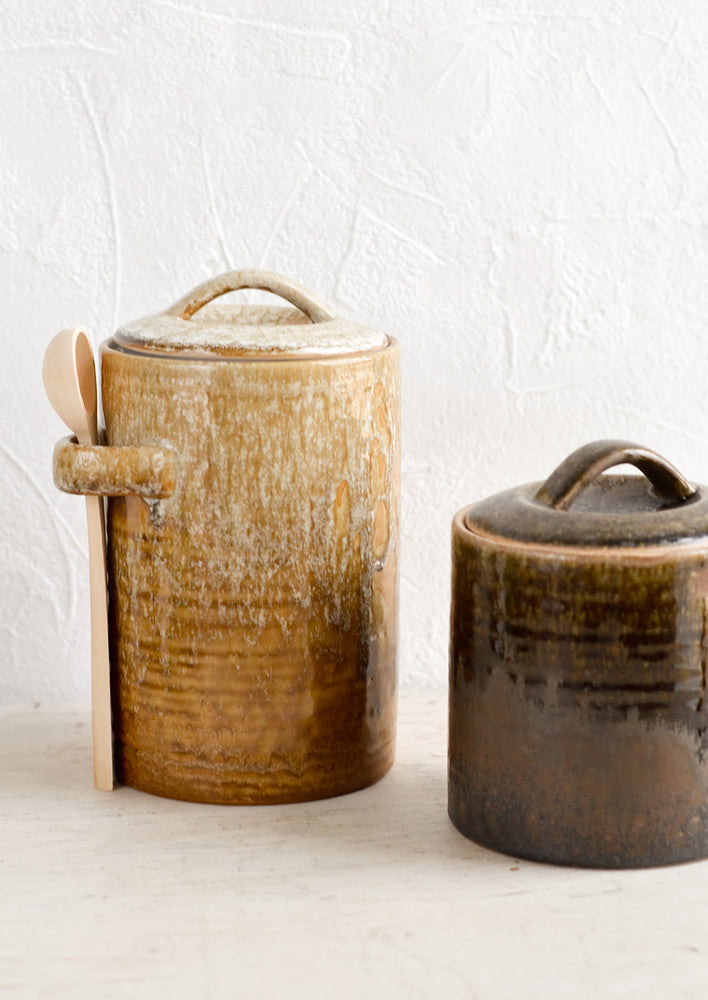 1: Two ceramic storage jars in short and tall sizes, glazed in light and dark brown glazes.