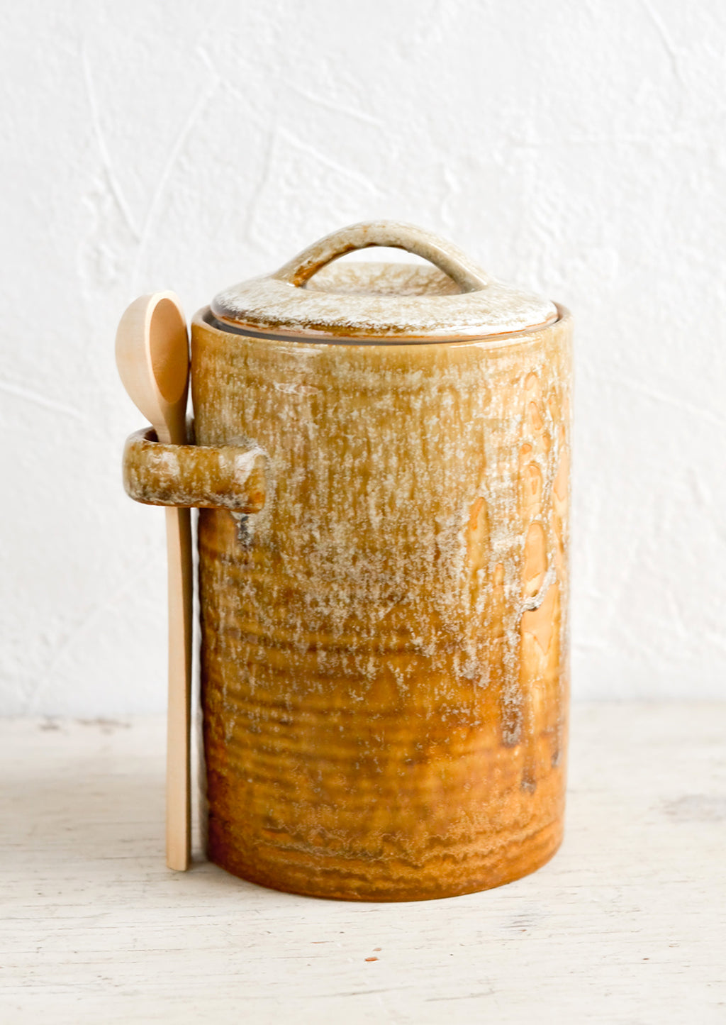 Tall / Light Brown: A ceramic storage jar in rustic light brown glaze with a wooden spoon on the side.