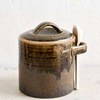 Short / Dark Brown: A ceramic storage jar in a rustic dark brown glaze with a wooden spoon on the side.