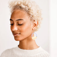 3: Model wearing blue and brass circular earrings