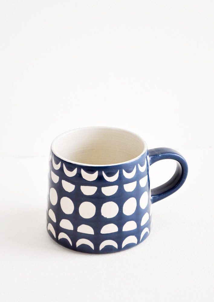 1: Ceramic mug in navy blue glaze with allover white moon phases print